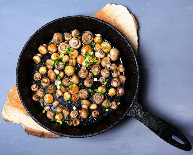 Champignons champignons frits dans une poêle en fonte avec des oignons verts frais sur un support en bois sur un fond gris avec copie espace vue de dessus.