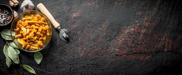 Champignons en conserve dans un bol avec un ouvre-bouteille, feuille de laurier et épices sur table rustique sombre.