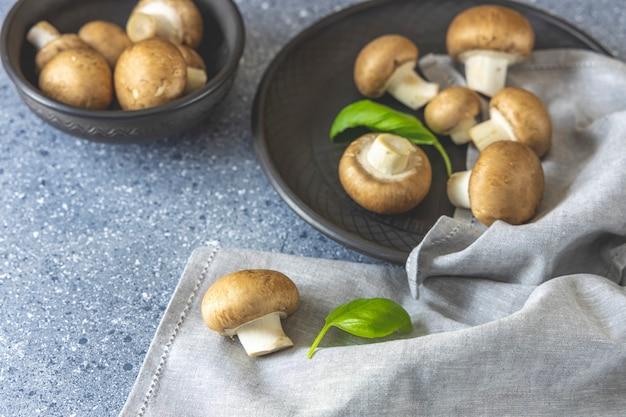Champignons crus sur des plaques noires sur fond gris avec un torchon de cuisine gris