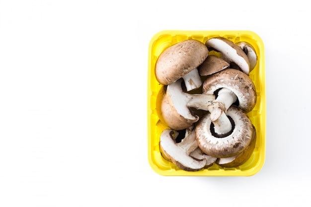 Champignons dans une boîte jaune sur blanc