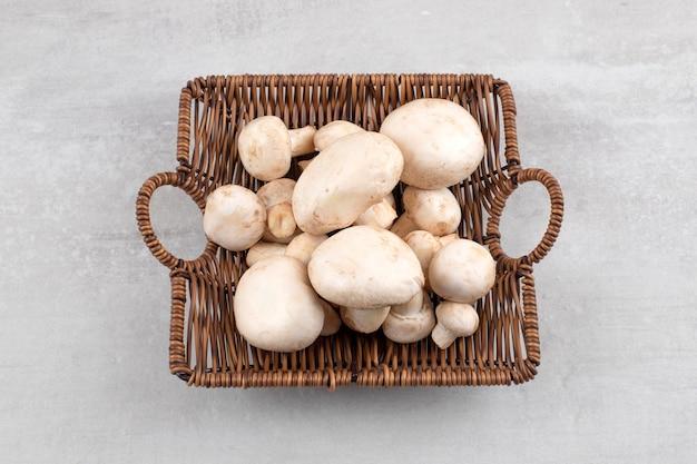 Champignons dans un panier en osier, sur la table en marbre.