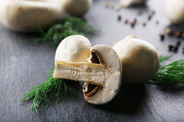 Champignons, épices et aneth sur fond de bois gris