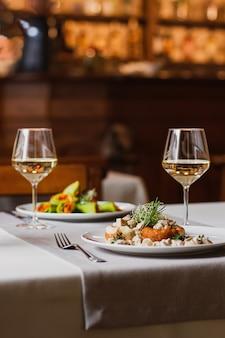 Champignons farcis remplis de fromage, tige de champignon et microgreen sur la plaque blanche avec un verre de vin dans le restaurant