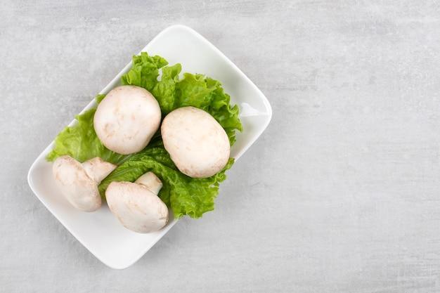 Champignons sur une feuille de laitue sur une assiette, sur la table en marbre.