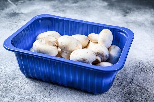 Champignons frais dans des emballages en plastique.