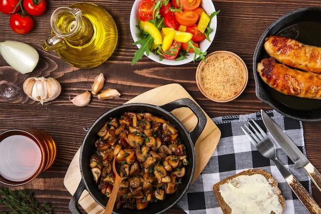 Champignons frits et saucisses dans une poêle en fonte. ingrédients pour la cuisine simple et rustique, vue d'en haut.