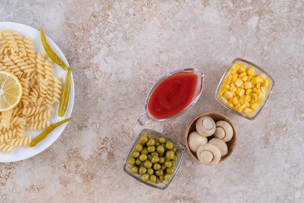 Champignons, grains de maïs, pois verts et ketchup portionnés à côté d'un plateau de pâtes sur une surface en marbre