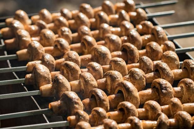 Champignons grillés sur des brochettes cuites au brasier, gros plan.