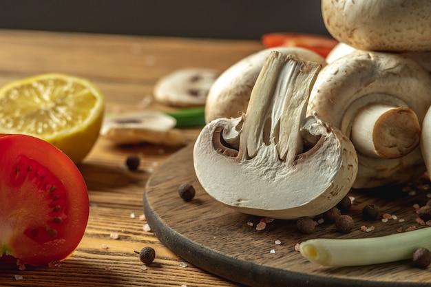 Champignons, légumes, citron et épices sur une table en bois. concept d'ingrédients pour cuisiner un plat délicieux.