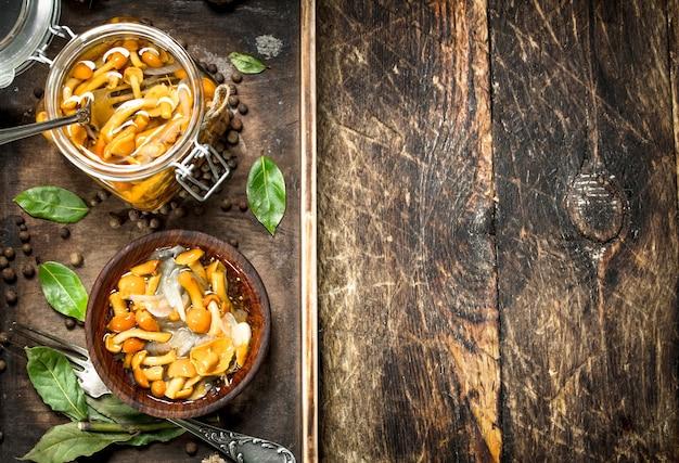 Champignons marinés dans un bol avec des épices et des herbes sur une table en bois.