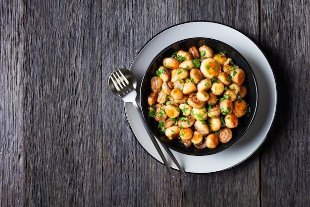 Champignons marrons à l'ail espagnol tapas al ajillo champignons ail rôti avec persil, jus de citron sur une plaque noire sur une table en bois sombre, vue de dessus, mise à plat, espace copie