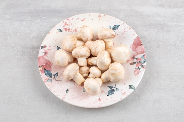 Champignons mûrs sur une assiette, sur la table en marbre.