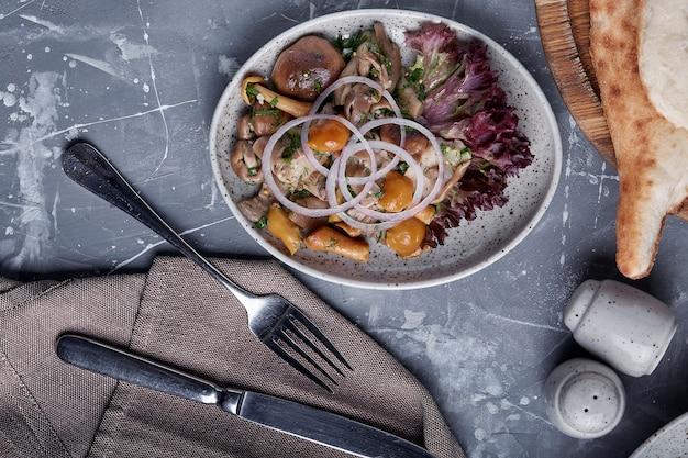 Champignons et oignons marinés dans une assiette sur fond gris