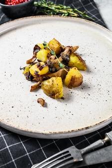 Champignons pleurotes avec pommes de terre et thym. fond gris. vue de dessus