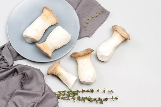 Champignons pleurotes roi sur plaque en céramique grise et sur table