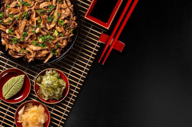 Champignons shimeji dans une poêle en fer avec du gingembre, du wasabi et du sunomono dans un fond noir.