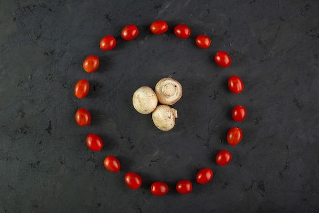 Champignons et tomates champignons mûrs avec tomates cerises moelleuses de forme ronde sur fond gris
