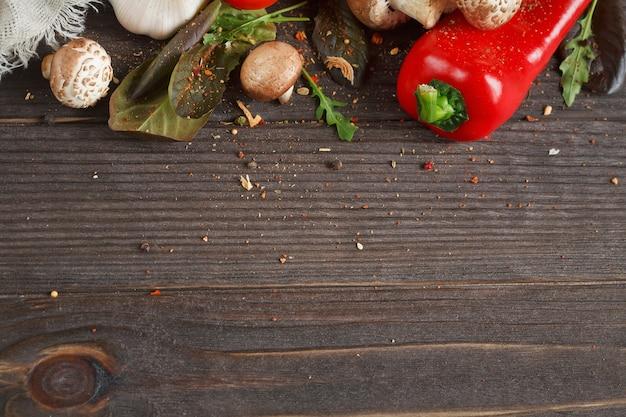 Champignons, tomates, poivre et ail sur une table en bois