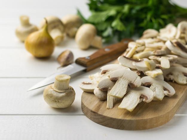 Champignons tranchés frais sur une planche à découper et oignons et herbes sur une table en bois blanc