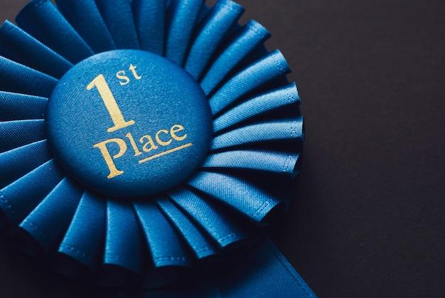 Champion 1ère place rosette bleue avec texte doré sur fond noir