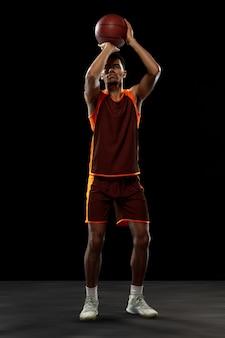 Champion. jeune joueur de basket-ball afro-américain déterminé, s'entraînant en action, mouvement isolé sur fond noir. concept de sport, mouvement, énergie et mode de vie sain et dynamique.