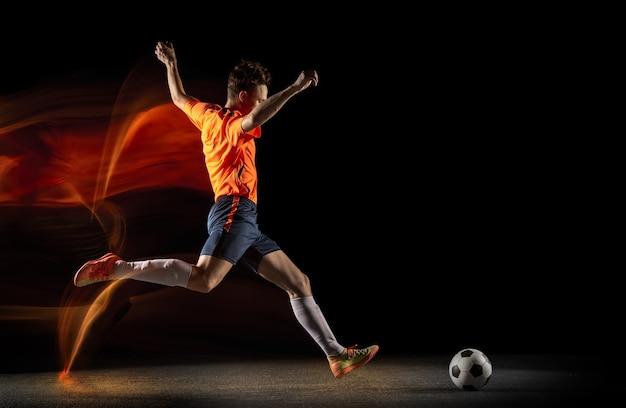 Champion. jeune joueur de football ou de football masculin caucasien en vêtements de sport et bottes frappant le ballon pour le but en lumière mixte sur fond sombre. concept de mode de vie sain, sport professionnel, passe-temps.