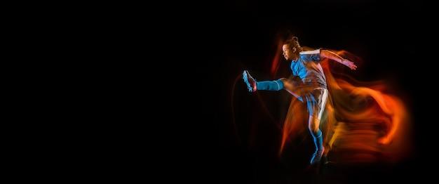 Champion. joueur de football ou de soccer sur fond de studio noir en lumière mixte. jeune modèle sportif masculin s'entraînant en action. frapper le ballon, attaquer, attraper. concept de sport, compétition. prospectus