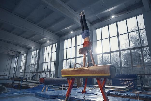 Champion. petit gymnaste masculin s'entraînant en salle de sport, flexible et actif. garçon caucasien, athlète en vêtements de sport pratiquant des exercices de force, d'équilibre. mouvement, action, mouvement, concept dynamique.