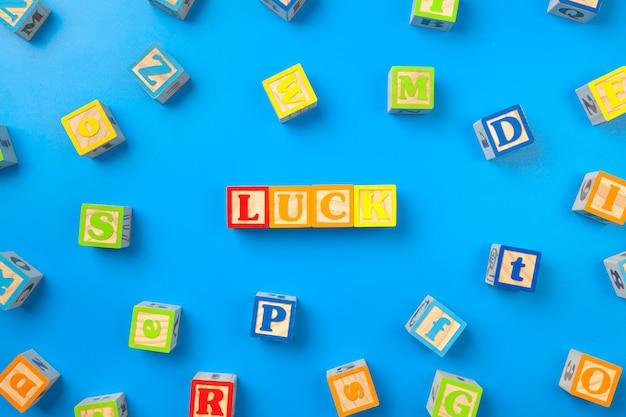 La chance. blocs d'alphabet coloré en bois sur bleu