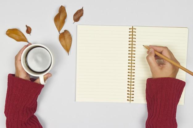 Chandail à porter à la main avec une tasse de café et écrire sur un cahier, feuilles d'automne sur le côté.