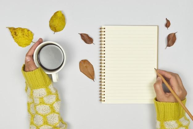 Chandail avec tasse de café et cahier, feuilles d'automne sur fond blanc