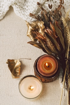Chandails chauds, bougies et bouquet de fleurs séchées
