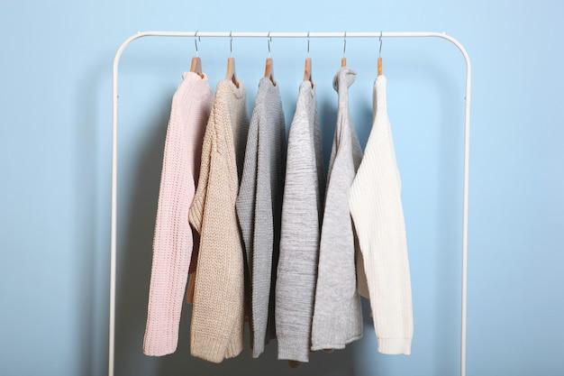 Chandails chauds sur un cintre de garde-robe sur un fond coloré