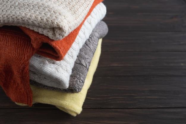 Chandails chauds tricotés pliés, demi-couvertures ou couvertures. vêtements d'automne et d'hiver. place pour votre texte.