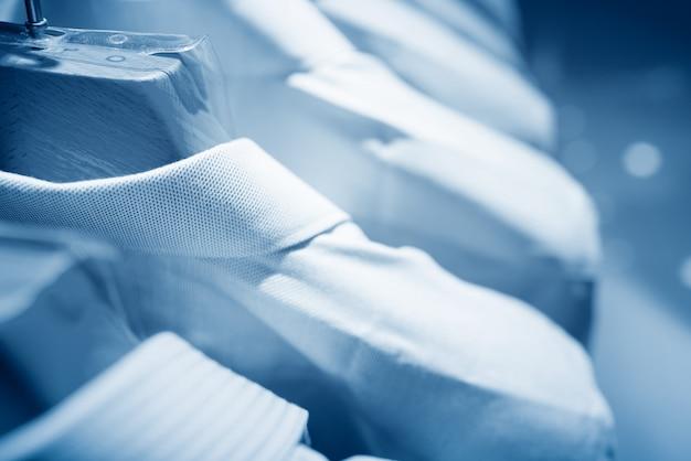 Chandails et chemises pour hommes de différentes couleurs sur des cintres dans un magasin de vêtements de détail
