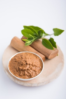 Chandan ayurvédique ou pâte de bois de santal dans un bol en argent avec des feuilles de bâtons et de feuilles placées sur sahanor sahana ou une base en pierre circulaire pour créer de la pâte