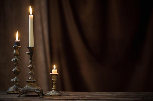 Chandelier antique avec bougie allumée sur la vieille table en bois sur rideau de velours marron