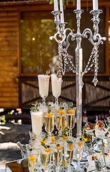 Chandelier et trois lignes verticales de verres à champagne en cristal. décoration riche et tendance. fermer.