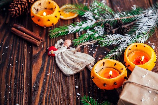 Chandeliers en mandarines avec branches de sapin, jouets et cadeaux sur une table en bois. noël et nouvel an