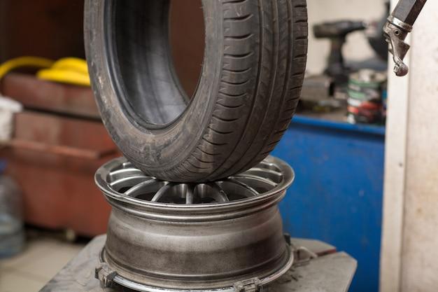 Changement de pneu de voiture de mécanicien. réparation de pneus de roue.