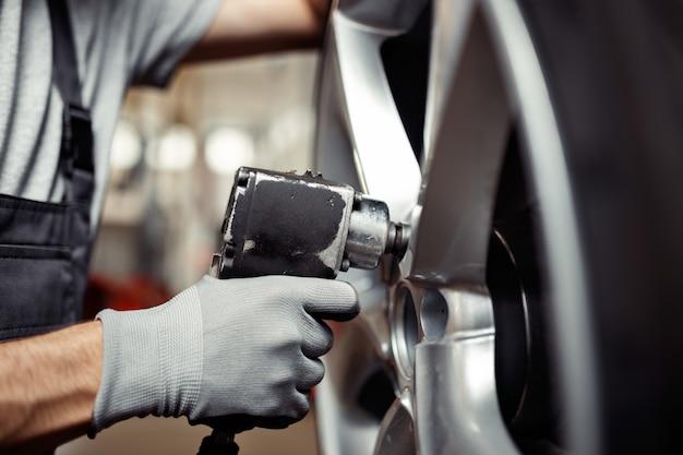 Changer un pneu dans un service automobile : atelier de réparation de véhicules.