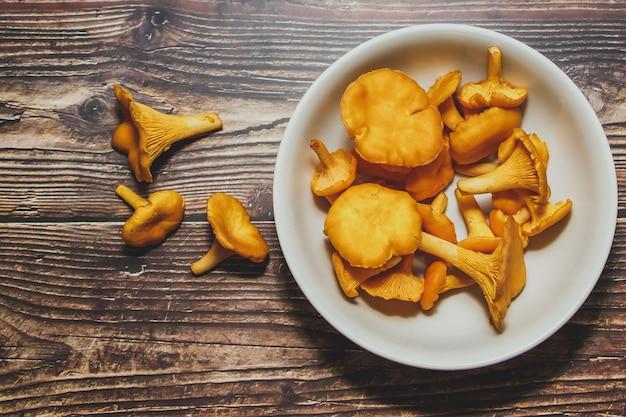 Chanterelles des bois dans une assiette blanche sur une table brune. nouvelle récolte, vue de dessus.