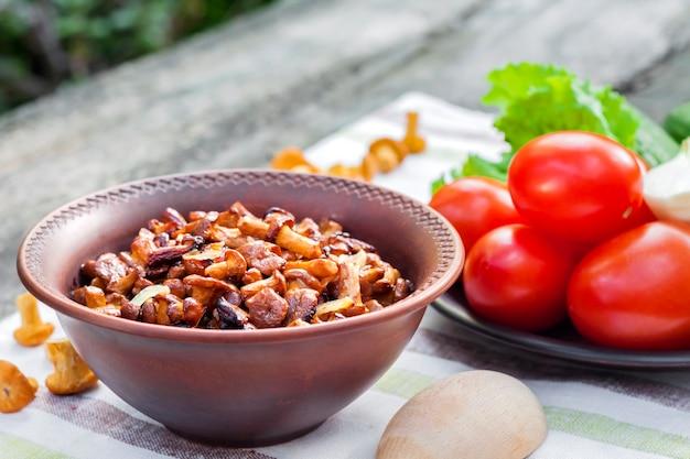 Chanterelles de champignons forestiers sauvages frits avec oignon dans un bol rustique