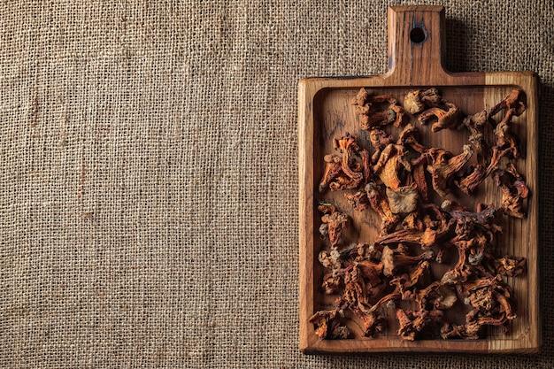 """Chanterelles séchées (cantharã """"â"""" llus cibã """"â rius), sur une planche de bois, sur une surface tissée rugueuse, toile de jute, vue du dessus"""