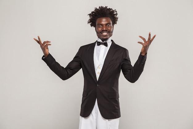 Chanteur ou acteur africain bien habillé avec une coiffure afro en smoking de style classique et un nœud papillon souriant à pleines dents. intérieur, studio isolé tourné sur fond gris
