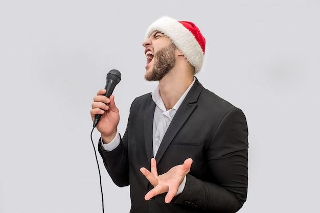 Chanteur adulte chantant une chanson au microphone. il crie et se déplace avec la main. jeune homme porte un costume et un chapeau de noël.