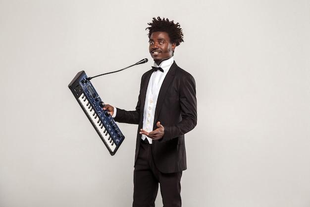 Chanteur africain à la mode avec une coiffure afro en smoking noir de style classique et noeud papillon tenant un synthétiseur, regardant la caméra. intérieur, tourné en studio isolé sur fond gris