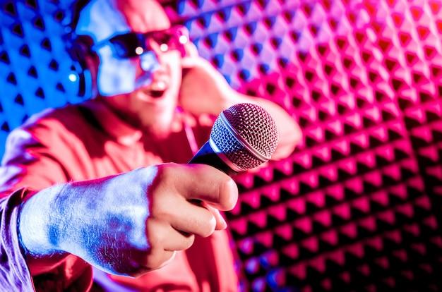 Le chanteur chante avec un microphone dans le studio d'enregistrement.