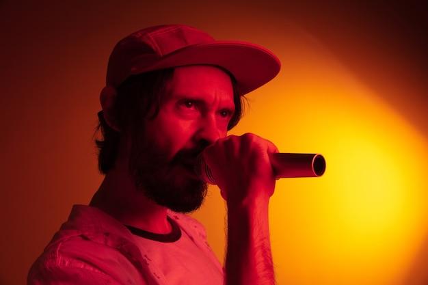 Chanteur d'homme jouant sur la lumière au néon