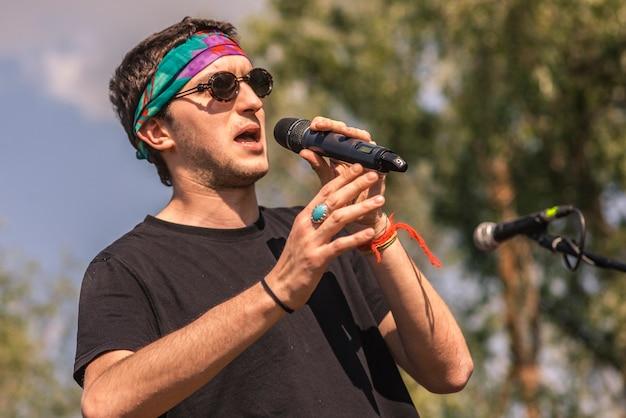Chanteur avec microphone à la main avec bouche ouverte